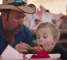 A father gives his son a hot KFC's drum stick chicken and his son blowing off it